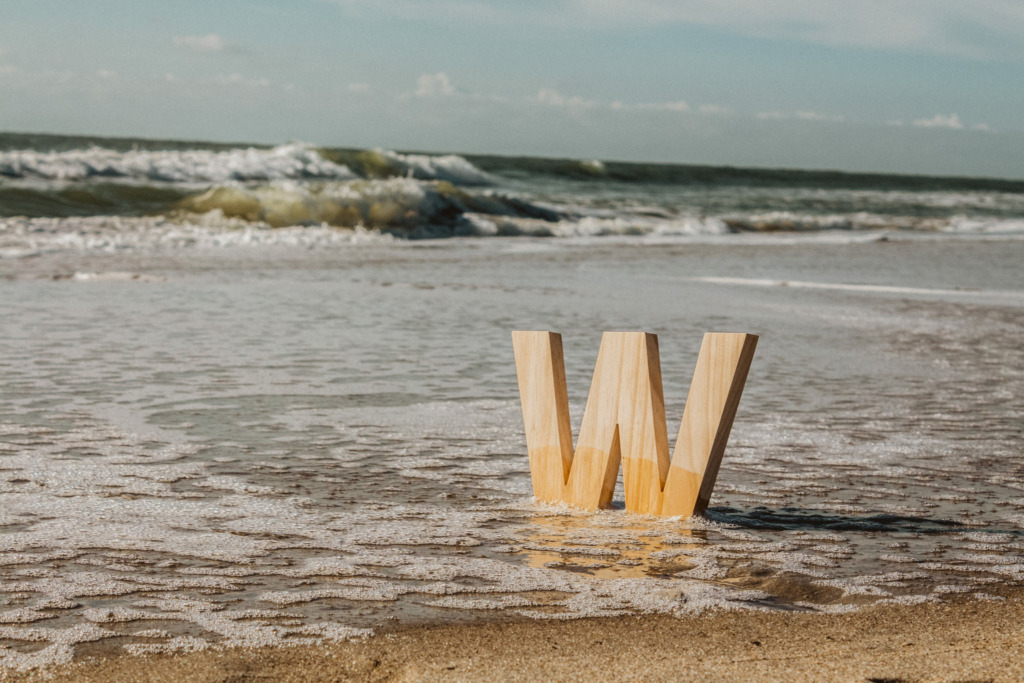 wooden carved 'W' in beach sand on the surf with blue skies and waves crashing in the background