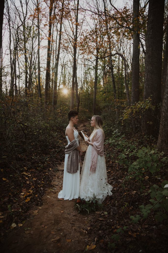 an elopement ceremony where two brides are standing on a leaf covered hiking trail in the middle of the woods with the sun setting behind them. each bride is wearing a white dress and neutral colored shaws