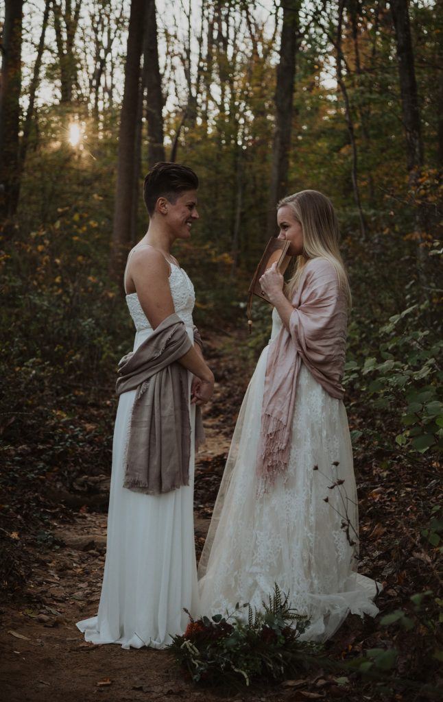 two brides are emotional while they say their vows to one another on their wedding day which is in the middle of the woods with the sun setting behind them