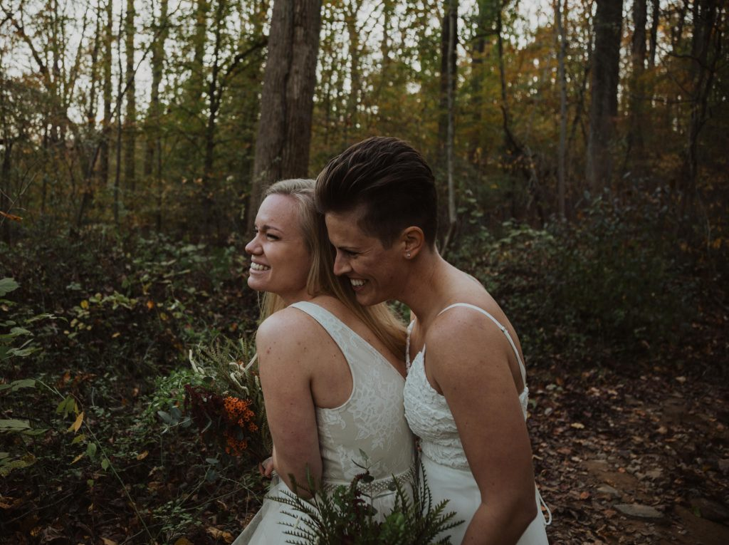 a LGBTQ+ couple hug one another in the woods