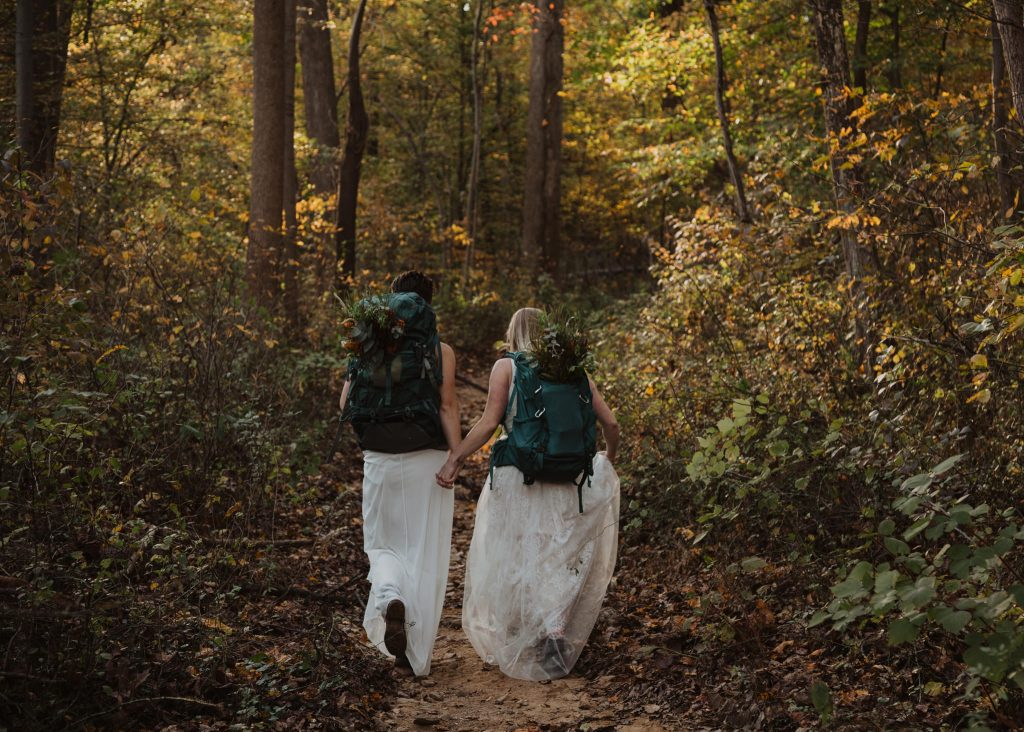 two brides wearing wedding dresses are wearing blue hiking backpacks and holding hands while they walk into the fall foliage woods in maryland