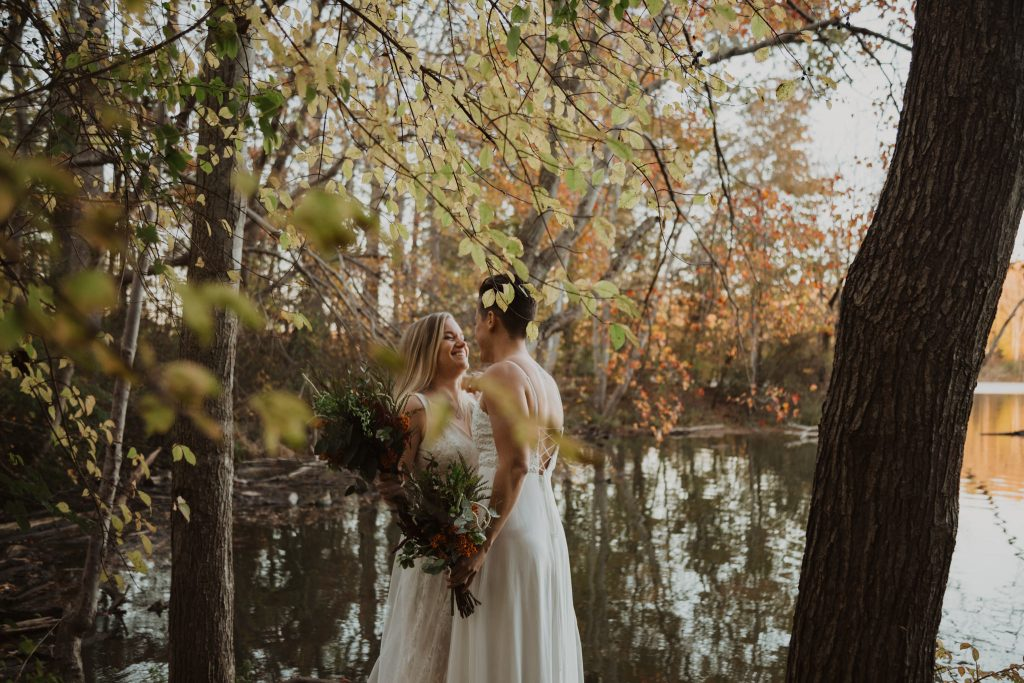 a LGBTQ+ couple wearing white wedding dresses stand along the edge of a lake with fall foliage surrounding them