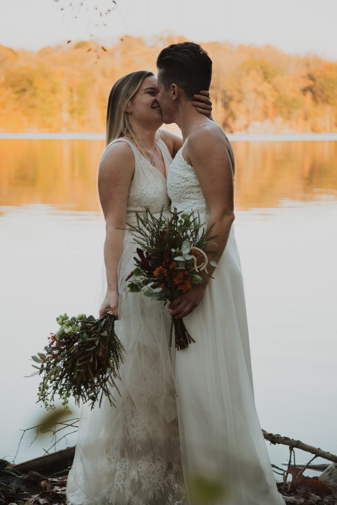 a bride and bride stand on the edge of a lake with the bright orange fall foliage in the background