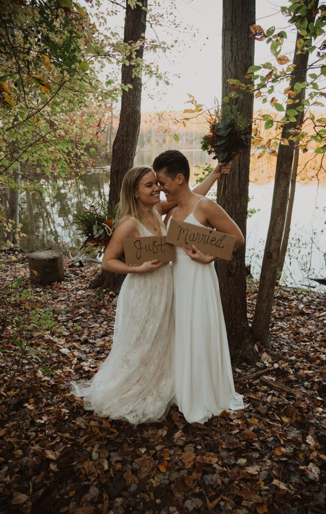 """two brides are hugging and holding a sign that read """"just eloped"""" next to a lake with fall foliage surrounding them"""