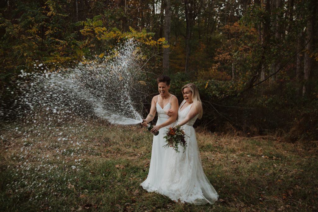 a bride and bride pop a bottle of champagne in the woods in the state of maryland to celebrate their elopement marraige