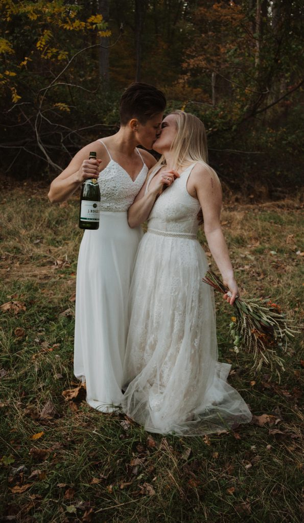 two brides kiss while holding a bottle of champagne in the middle of the woods to celebrate their maryland elopement