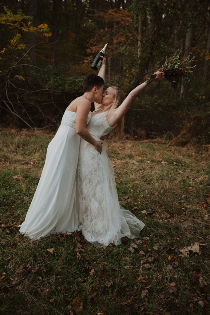 two brides kissing wile celebrating their recent wedding ceremony in the woods