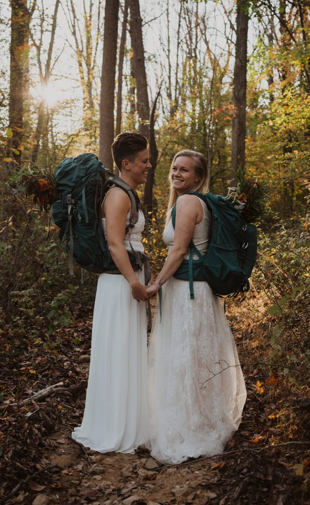 two brides wearing white wedding dresses are holding hands while wearing blue hiking backpacks