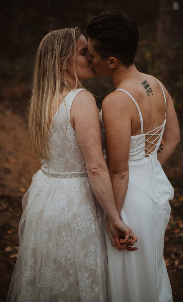 two brides are kissing and their backs are to the camera while they hold hands in the woods