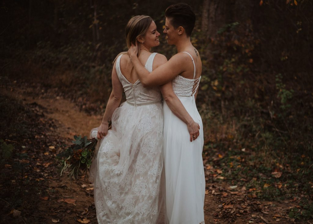 two brides wearing wedding clothes are standing on a leaf covered hiking trail kissing while the one grabs the others butt