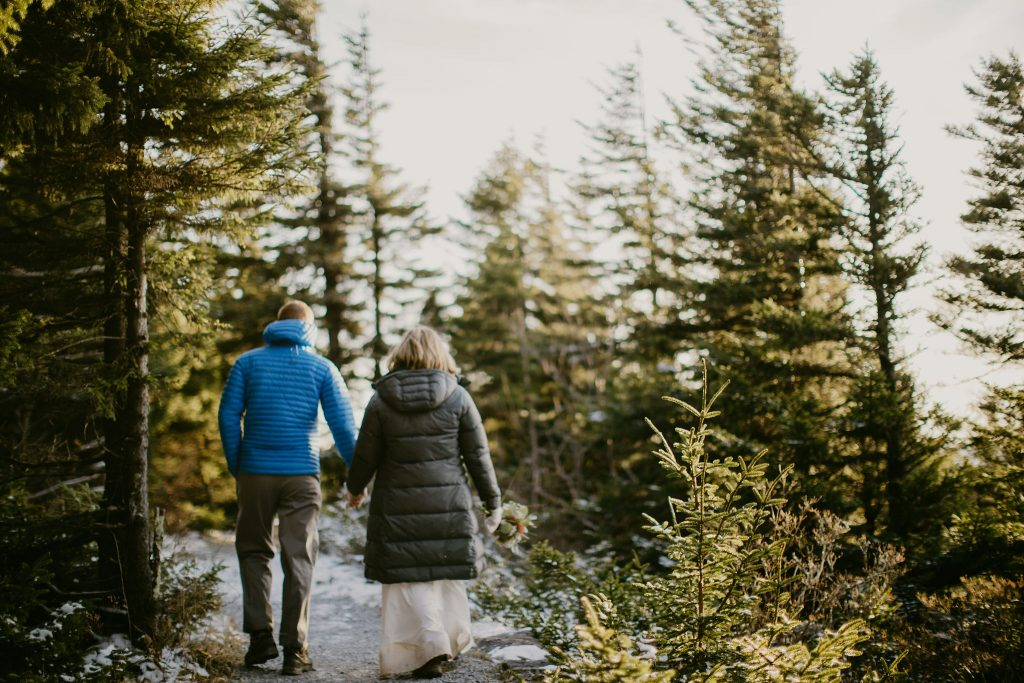 a bride and groom wearing wedding attire and big down jackets are walking hand in hand away from the camera on a snow covered trail surrounded by evergreens during golden hour