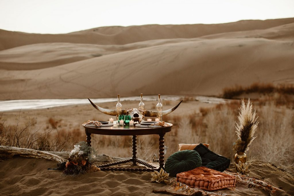 a picnic set up in the great sand dunes national park during sunset