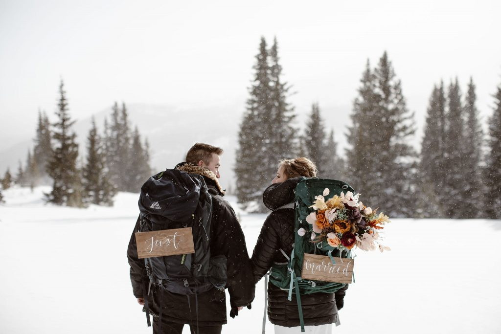 """a bride and groom are holding hands looking at each other with their backs to the camera while wearing hiking backpacks with signs that say """"just married"""""""