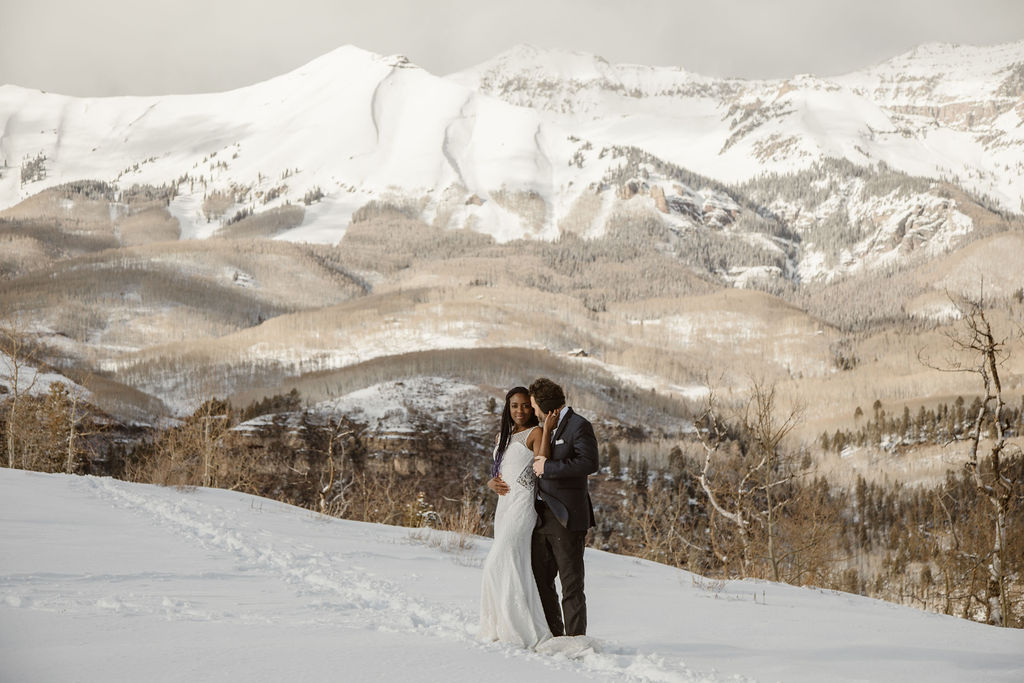 a bride and groom are hugging while standing in deep snow with a snow covered mountain in the background
