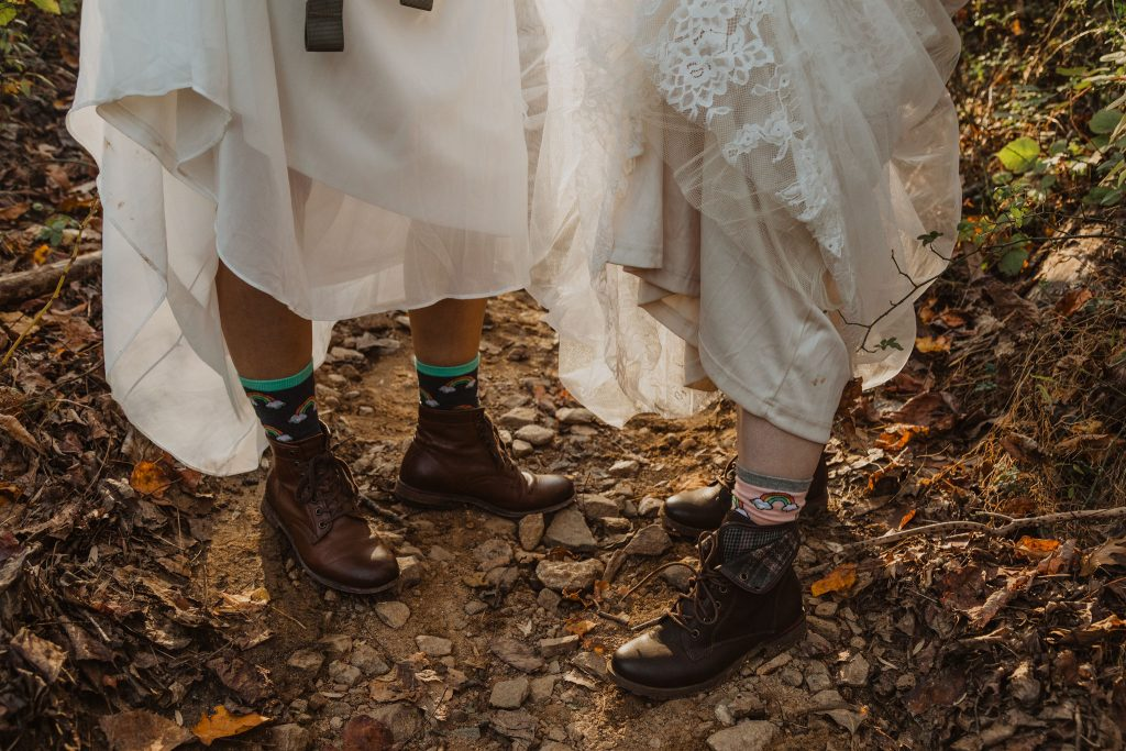 two brides wearing hiking boots and wedding dresses are standing on a leaf covered hiking trail in the woods and hiking up their wedding dresses to show off their gay pride socks