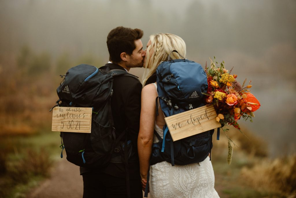 """a couple looking away from the camera kissing with their shoulders touching while wearing hiking backpacks with signs that say """"we eloped"""""""