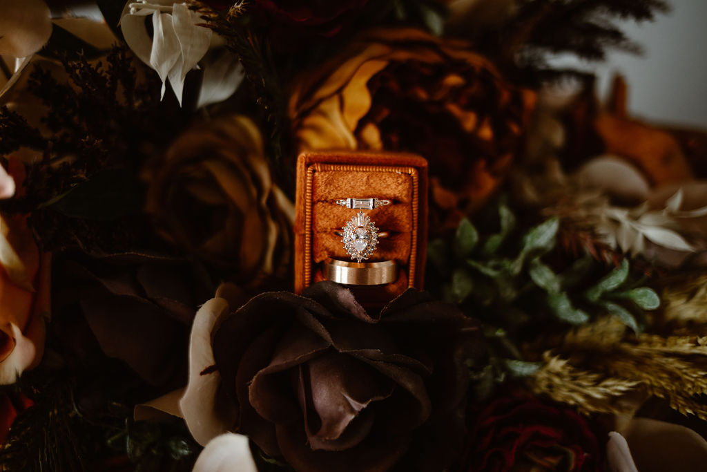 an orange ring box holding three wedding rings placed on top of a orange and purple floral bouquet