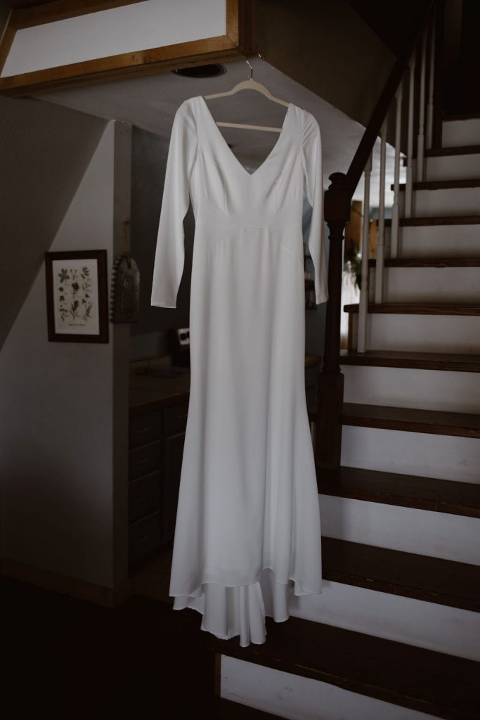 a long sleeve silk wedding dress hanging by stairs during the morning of a colorado winter elopement day
