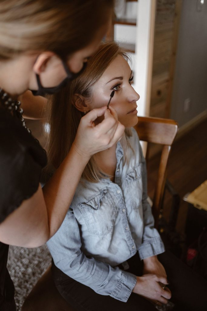 a bride getting her make up done on the morning of her wedding day