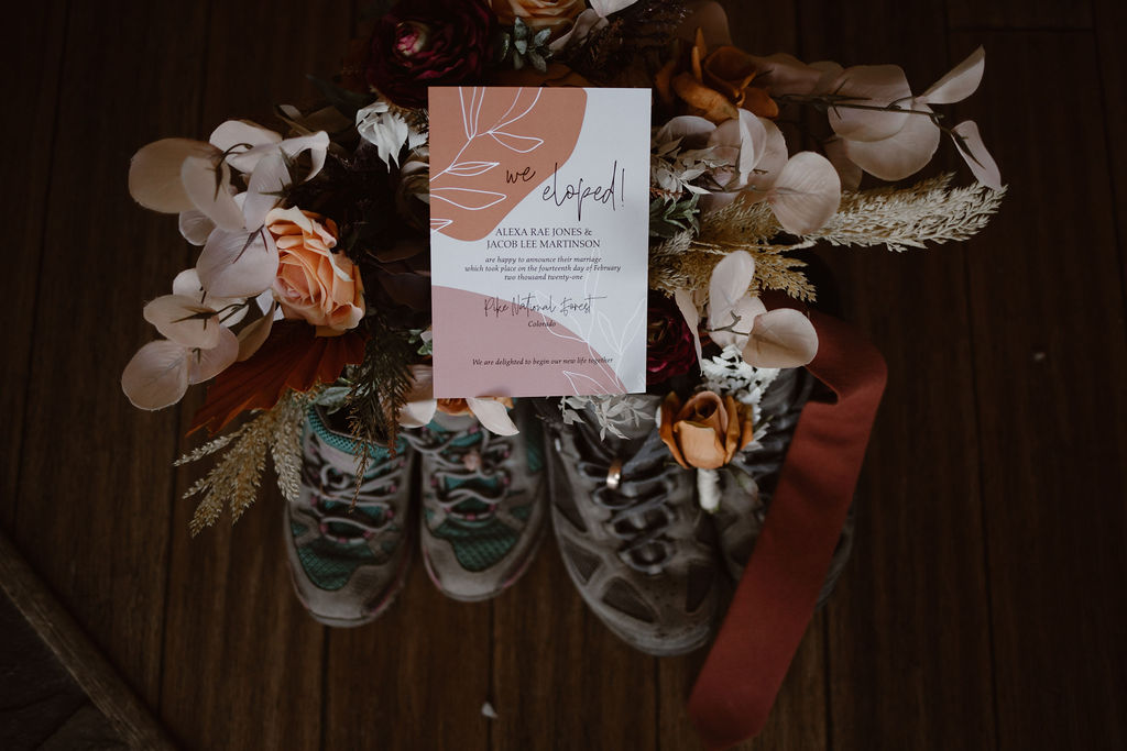 a detail shot of a colorado winter elopement including hiking boots, stationery, and florals
