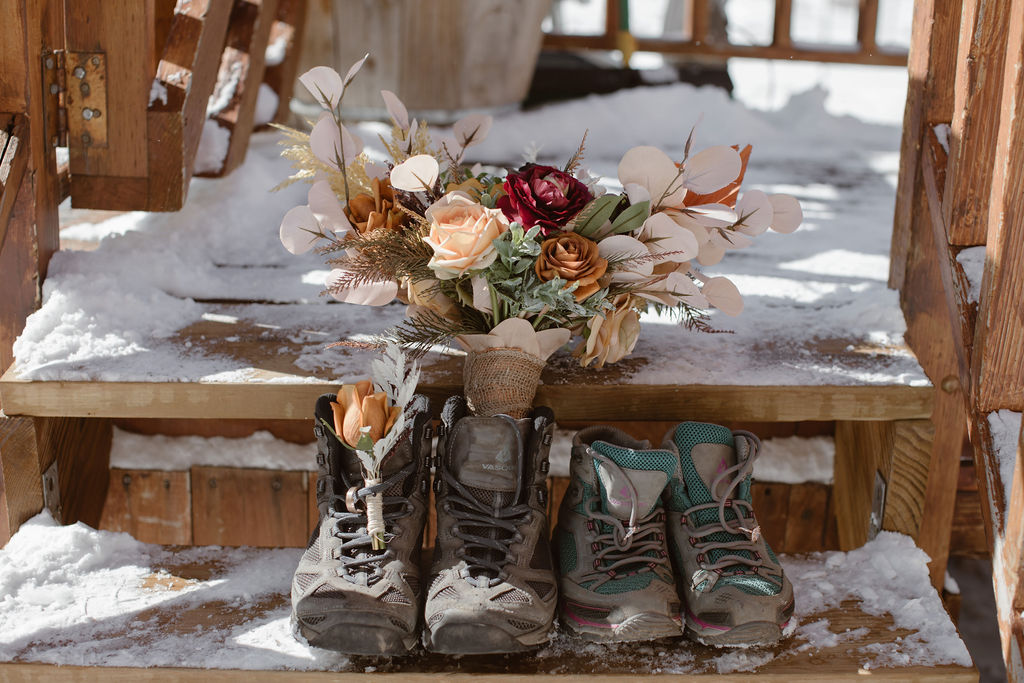 a detail shot of hiking boots, elopement stationery, and floral bouquet sitting on a snow covered outside wooden steps