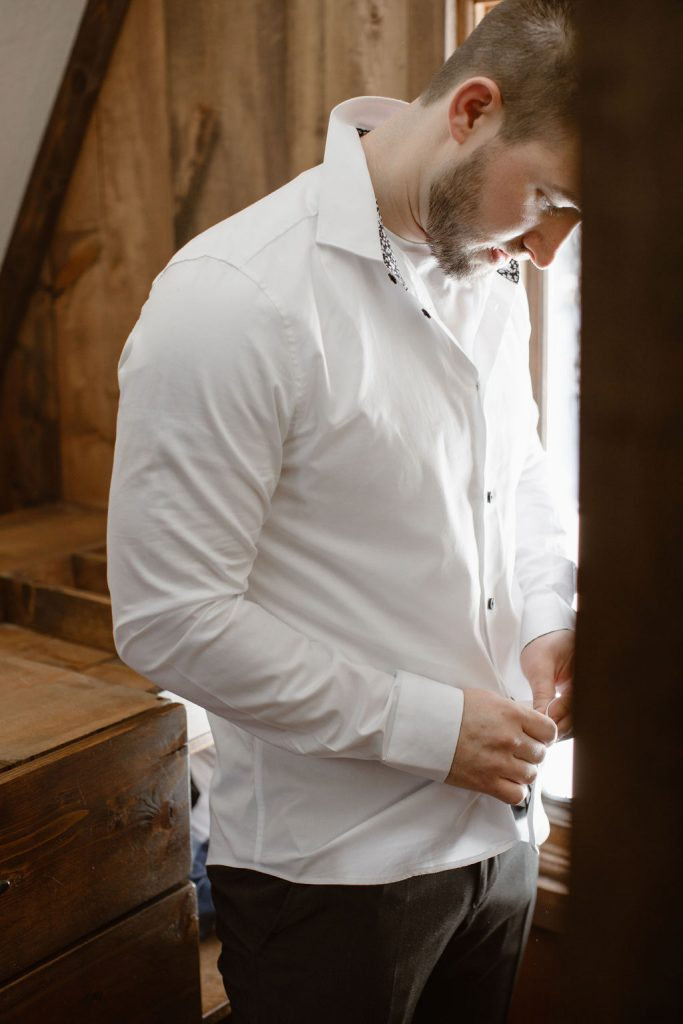 a groom buttoning up a white shirt