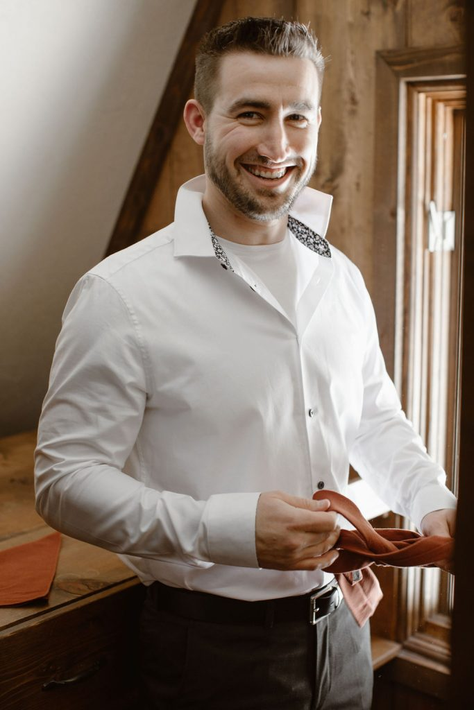 a groom getting ready for his colorado winter elopement