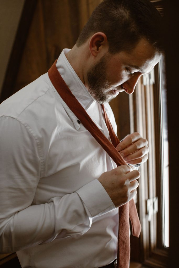 a groom putting on his tie and getting ready for his colorado winter wedding