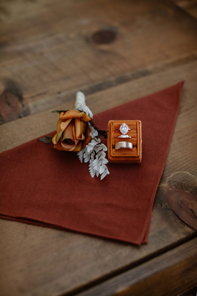 an orange pocket square with an orange rose and ring box