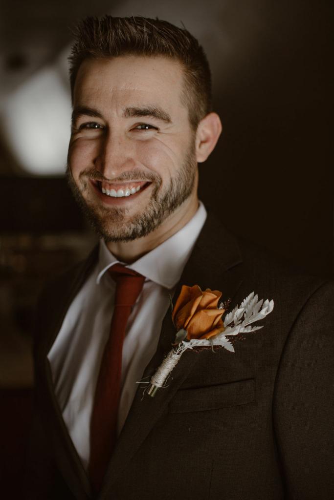 a portrait of a white male wearing black and orange wedding attire