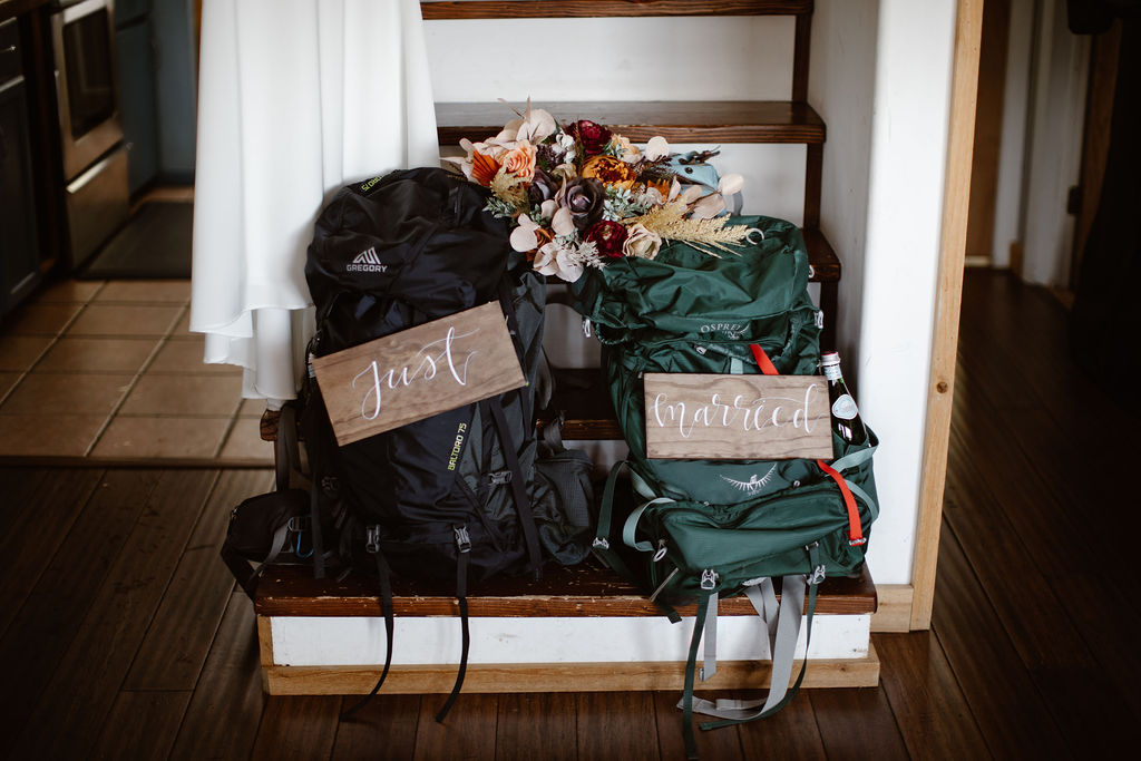 """two hiking back packs with signs that say """"just married"""" sitting on inside steps"""