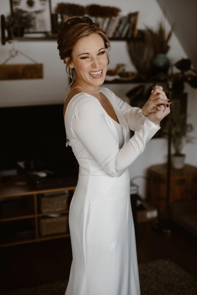 a white women wearing a long sleeve white wedding dress smiling