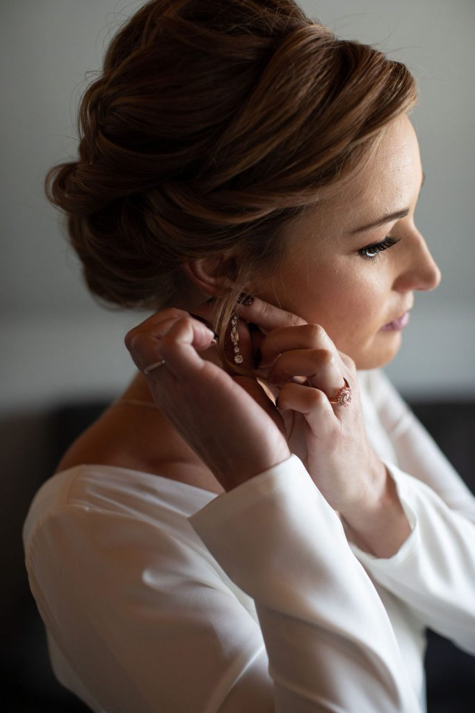 a white women putting on earrings while getting ready for her colorado winter wedding