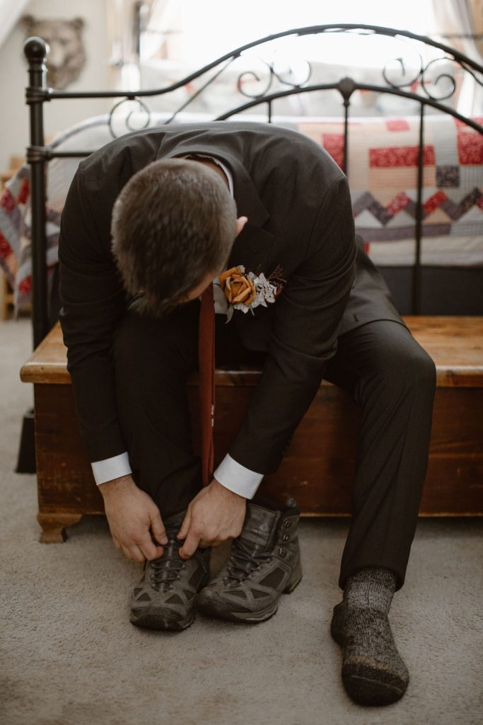 a white male tying his hiking boots dressed in wedding attire on the morning of his colorado winter wedding