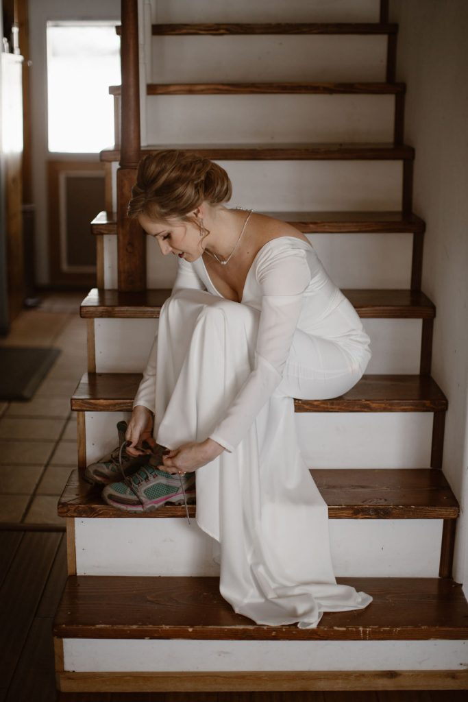 a white women sitting on inside stairs while wearing a long sleeve white wedding dress and tying her hiking boots