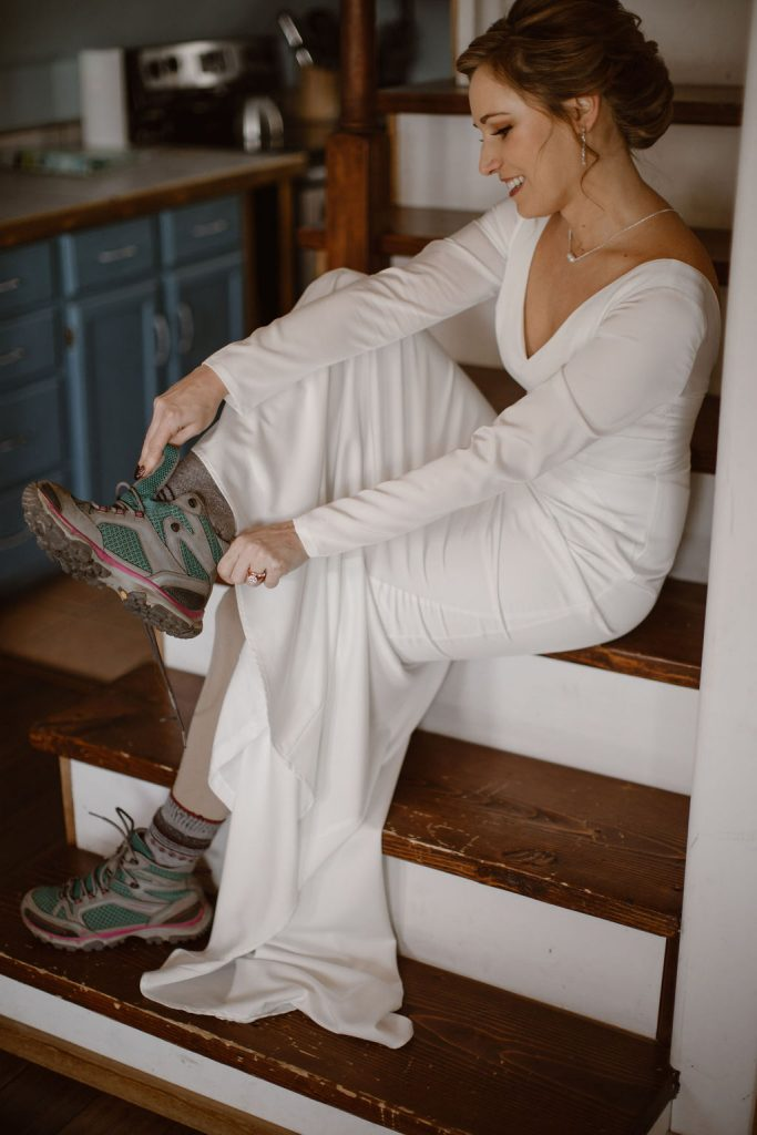 a white women sitting on inside stairs while wearing a long sleeve white wedding dress tying her hiking boots