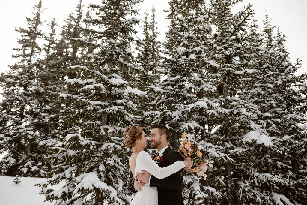 a bride wearing a long sleeve white silk wedding dress and groom wearing a black suit are hugging in front of snow covered evergreens