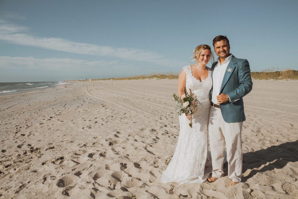 a bride and groom stand along the beach shore in the sand while hugging and smiling right after getting married