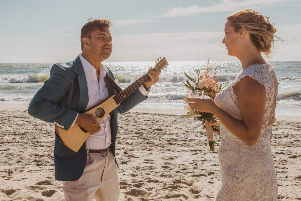 a couple wearing wedding attire celebrating on a sandy beach while the groom plays an acoustic guitar and the bride dances while holding champagne in the sand with the blue sky and waves in the background