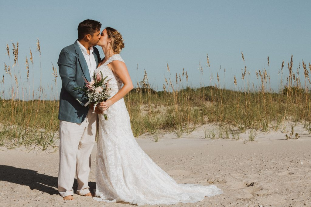 a groom wearing a blue sports jacket and linen beach pants kissing his bride whos wearing a lace wedding gown while standing in the sand with blue skies and a sand dune behind them