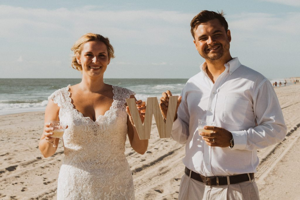 """a bride and groom are standing on a sandy beach with blue skies and waves behind them while holding a wooden """"w"""" and champagne"""