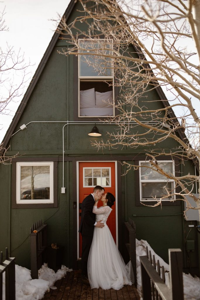 a couple wearing wedding attire standing outside of an A frame Cabin in Jefferson, Colorado on their elopement day
