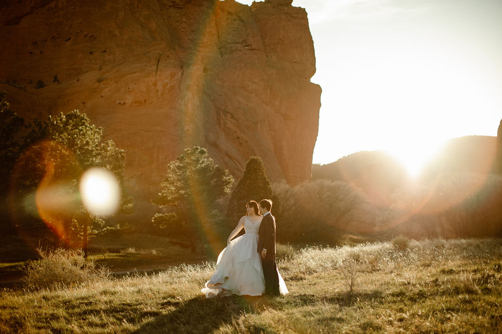 a couple wearing wedding attire is standing in a grassy field at the garden of the gods with tall red rocks behind them and the sun light creating beautiful lens flares on the image