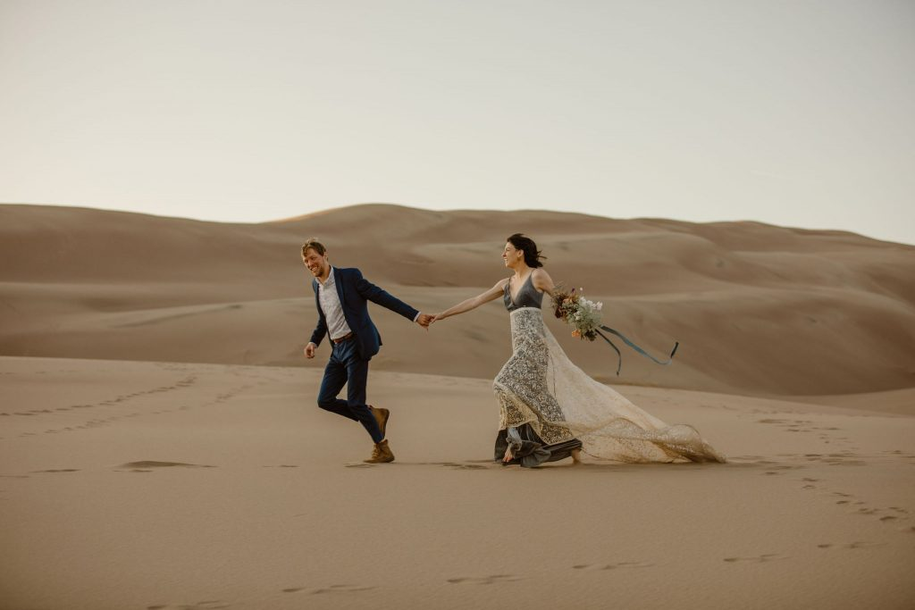 a bride and groom running hand in hand through the great sand dunes in colordao