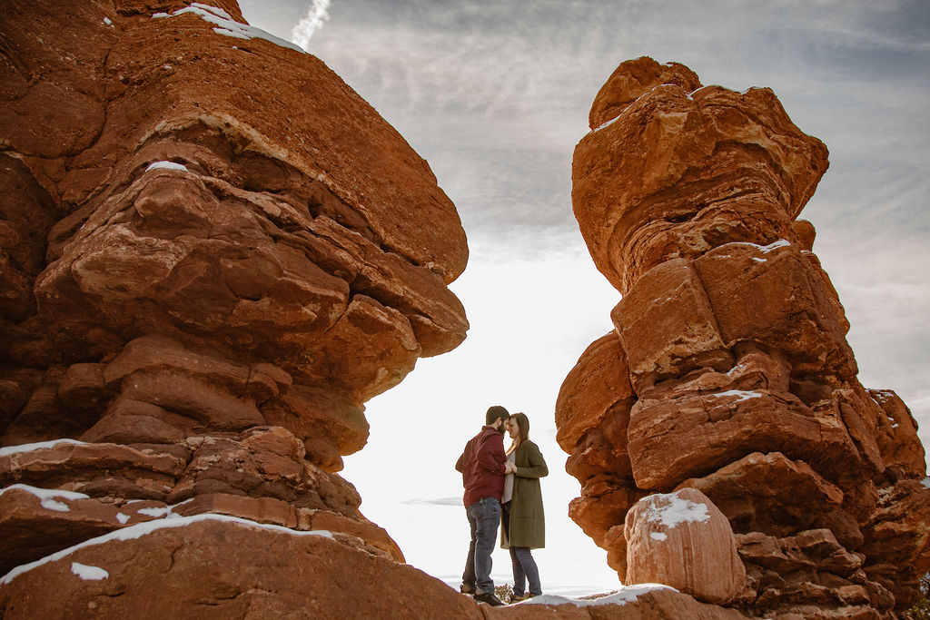 a young couple standing in between two rock formations at garden of the gods, colorado