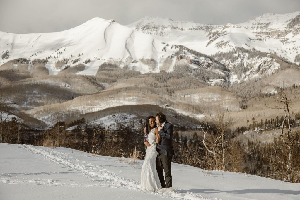 a couple standing in the snow on their elopement day with a snow covered mountain behind them