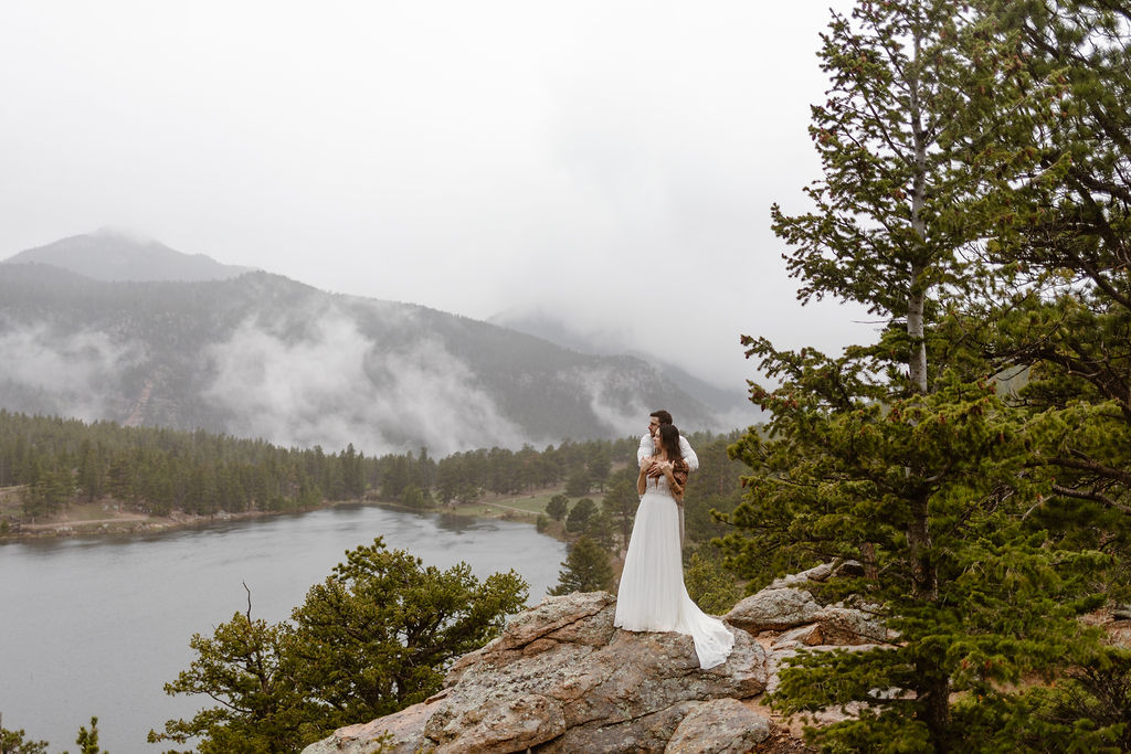 a male and female couple standing on a rock at an overlook in rocky mountain national park while wearing wedding clothes