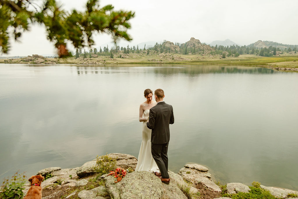 a couple wearing wedding attire are standing on a rock next to a lake during their elopement ceremony in colorado