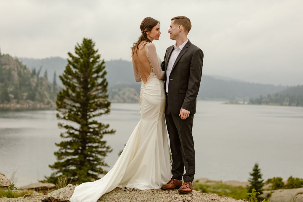 a female and male couple are standing on a rock in front of a lake with mountain views behind them