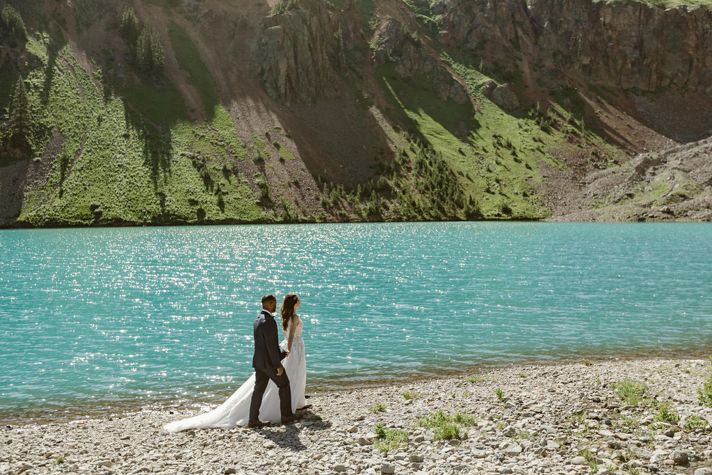 a couple wearing wedding attire are holding hands and walking along a turquoise blue lake shore in the san juan mountains